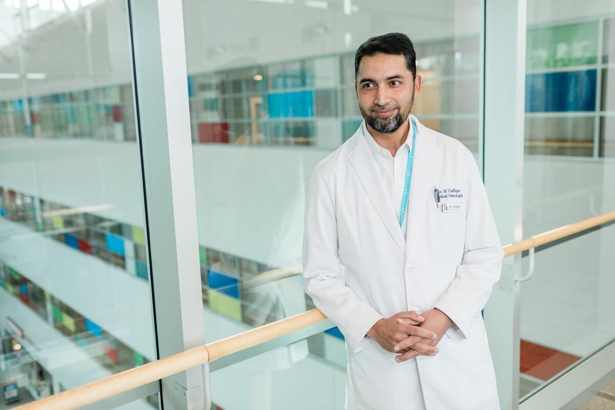 Doctor on white lab coat leaning on railing