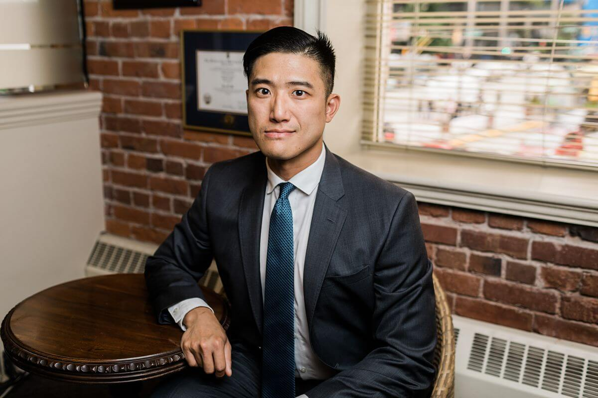 Headshot of lawyer sitting in an office in front of a brick wall